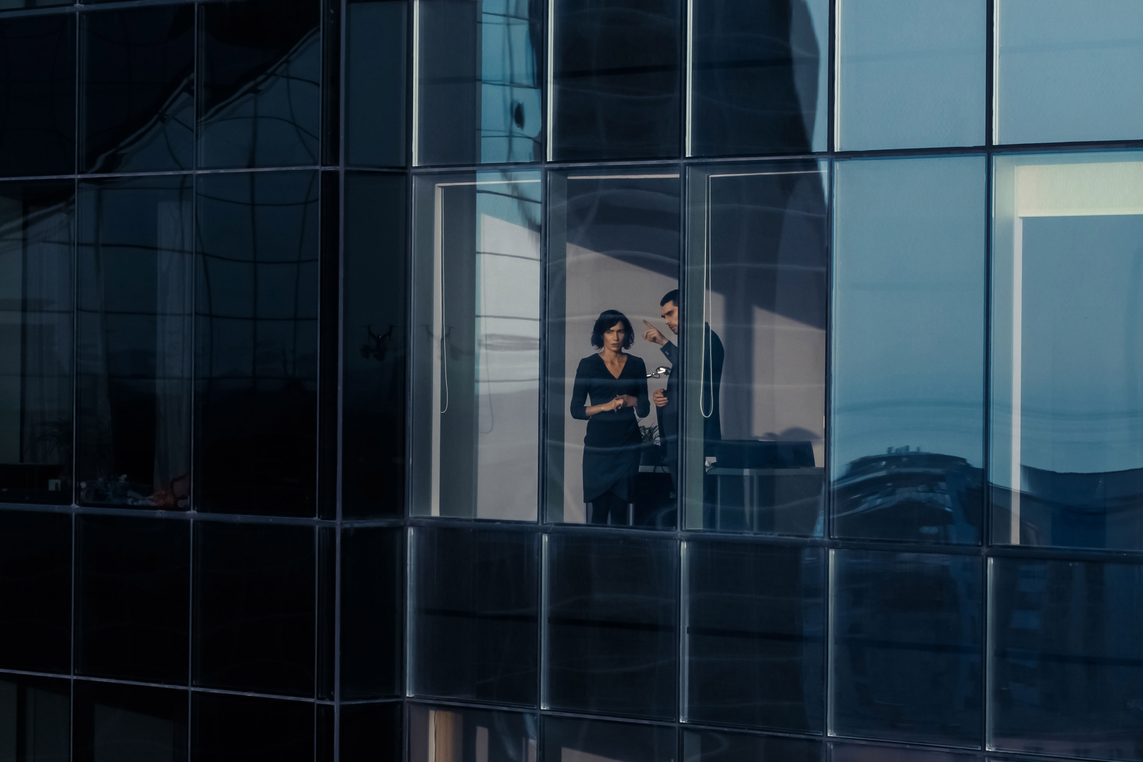 Man and woman point out office building window