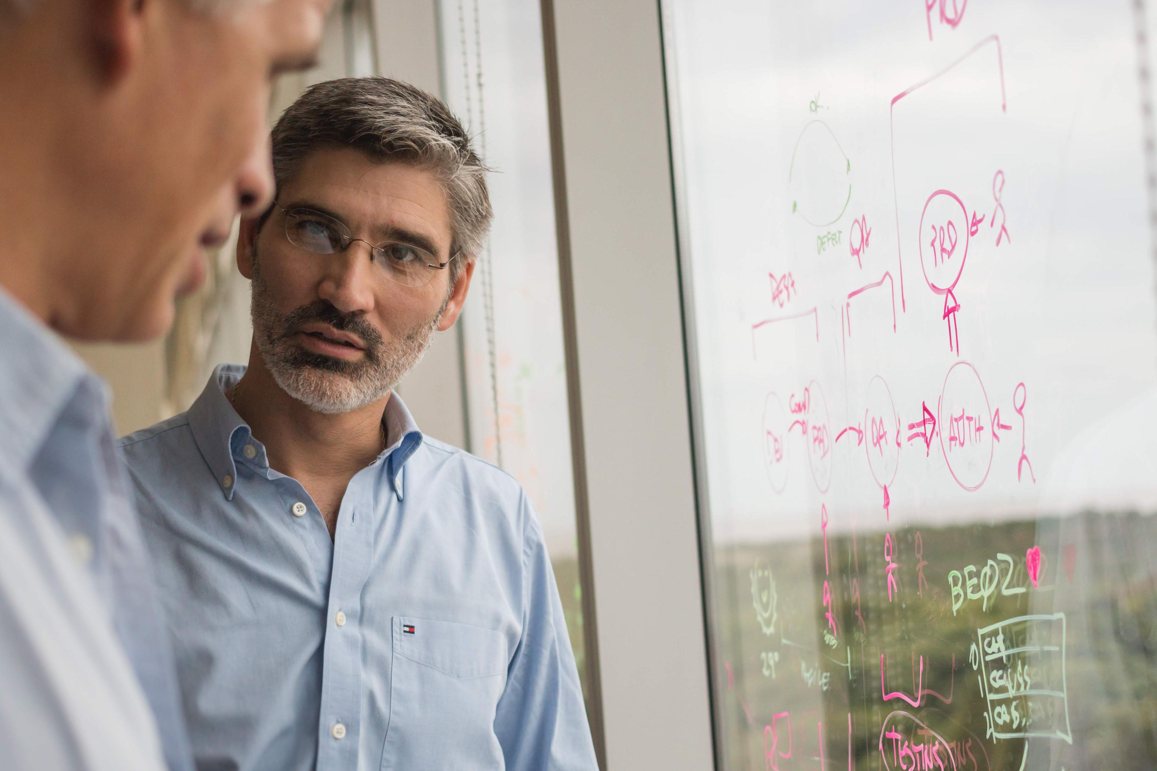 Hombre explicando un proceso escrito con fibra sobre una ventana