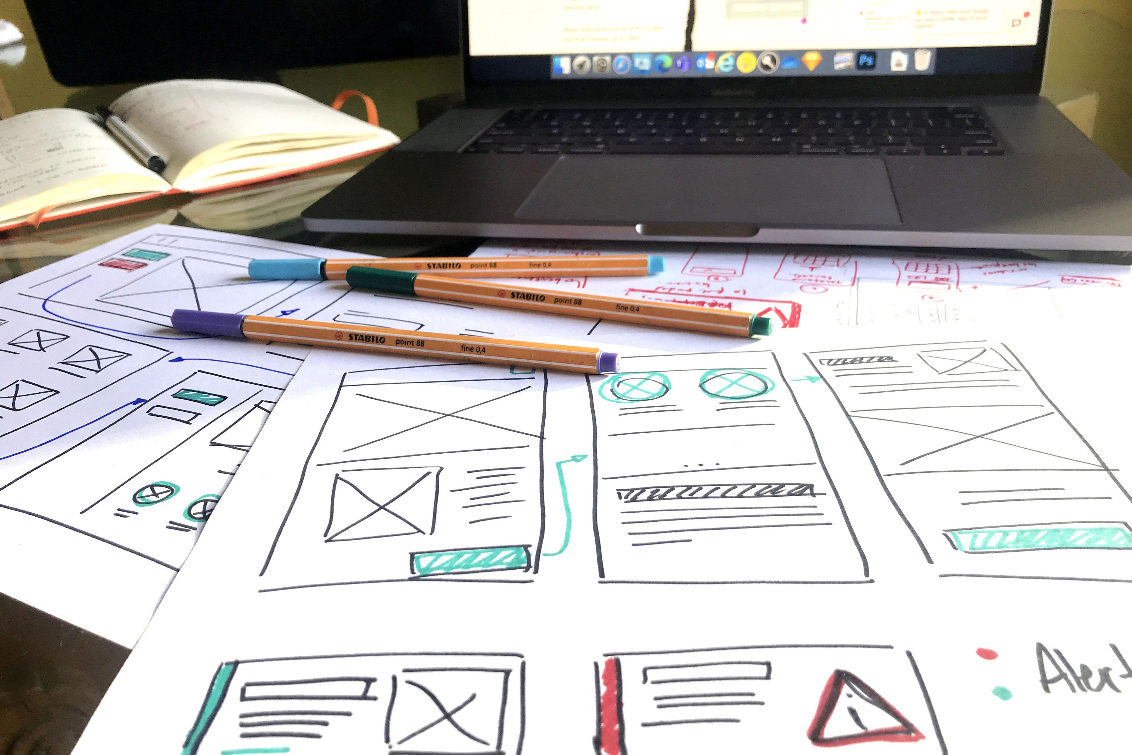 Wireframes de un diseño de una aplicación y una computadora portátil sobre una mesa