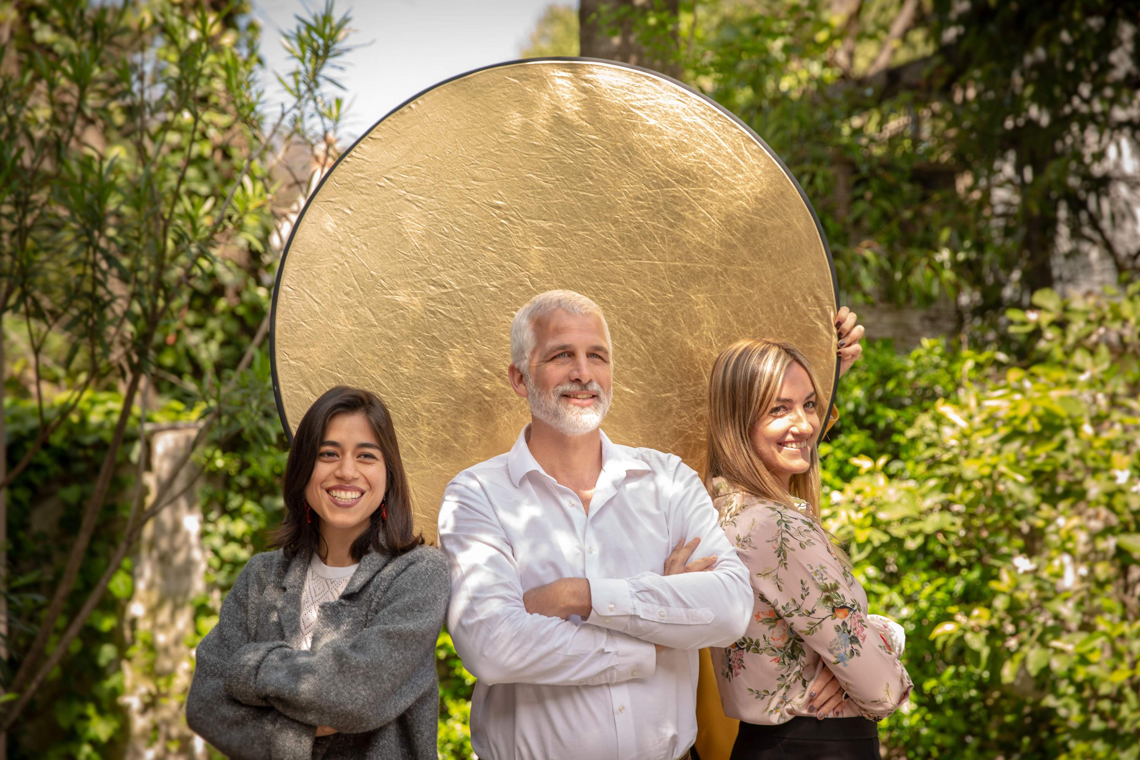 Tres personas posando delante de un panel circular dorado