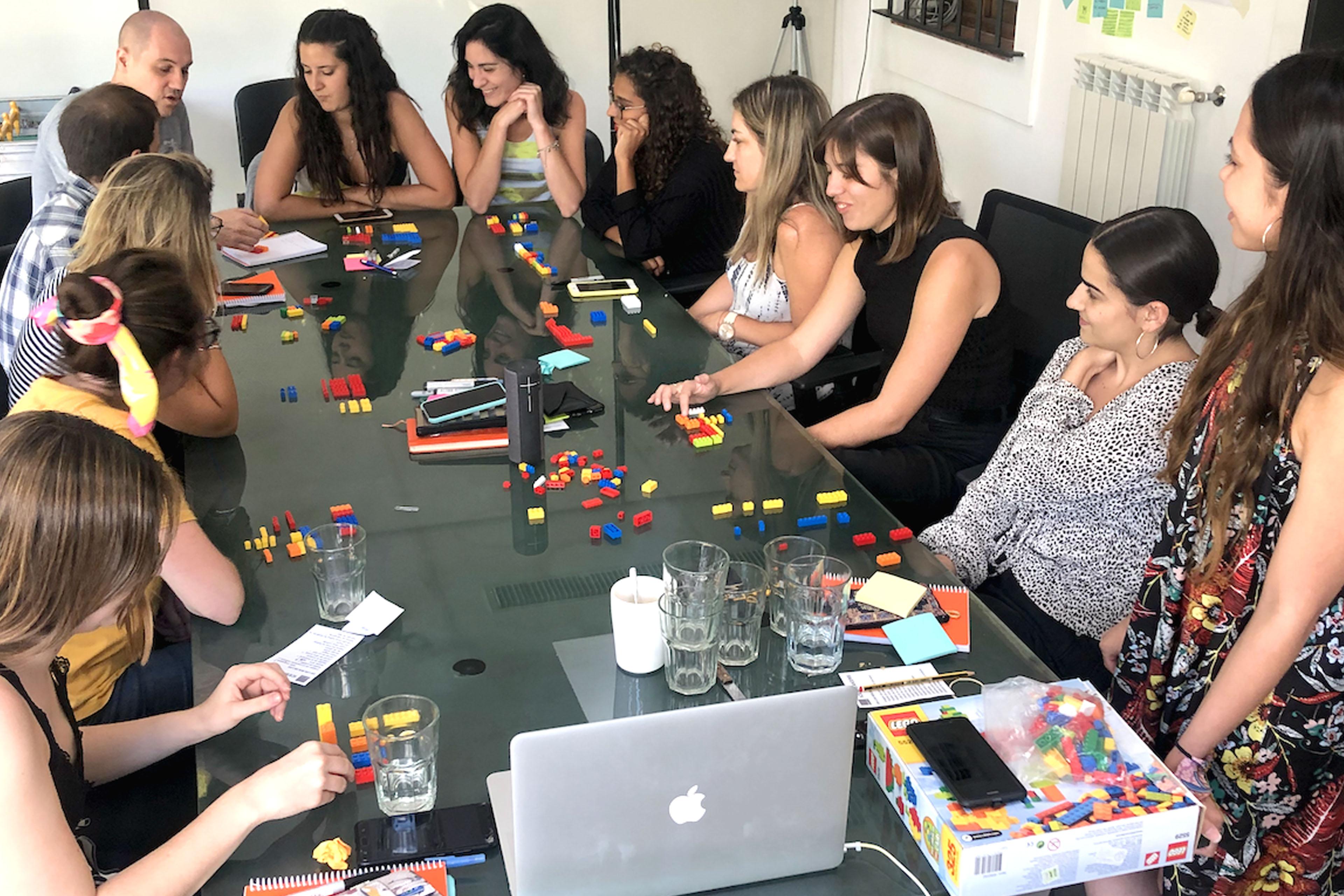 Equipo de 12 personas reunido alrededor de una mesa de trabajo