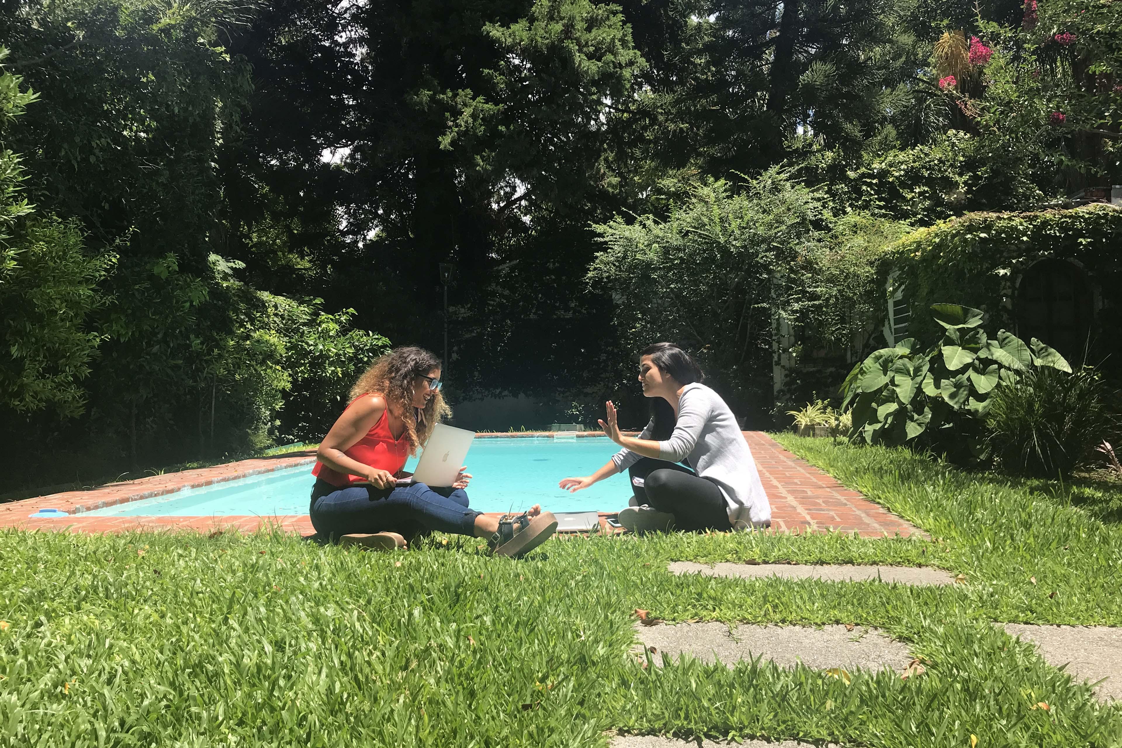 Dos chicas conversando sentadas en el suelo al lado de una piscina