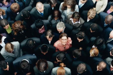 Mujer mirando hacia arriba entre un grupo de gente