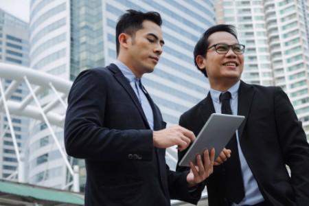 Hombres mirando la tablet con edificios de fondo