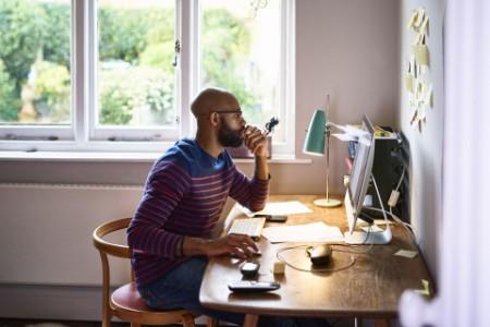 Hombre trabajando en una computadora portátil mientras está sentado en la cocina de su casa
