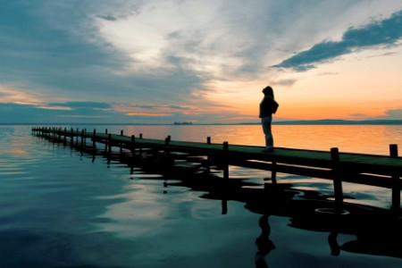 ey-silhouette-of-woman-on-lakeside-jetty-at-sunset