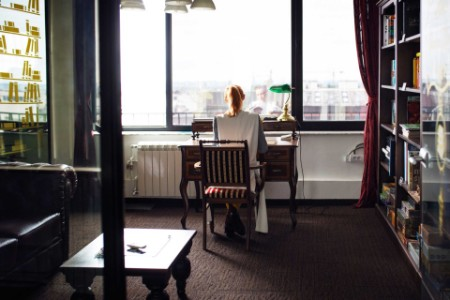 ey-woman-sits-at-a-desk-in-her-apartment