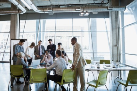 People in business meeting standing around computer