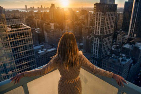 Woman at a balcony looking over a city