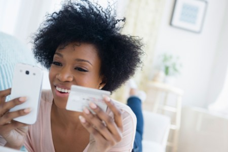 Woman smiling with a phone and a credit card