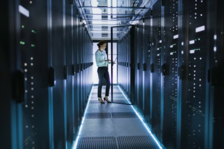 Female Server Technician Stands next to Cabinet in Data Center Corridor with Rows of Rack Servers