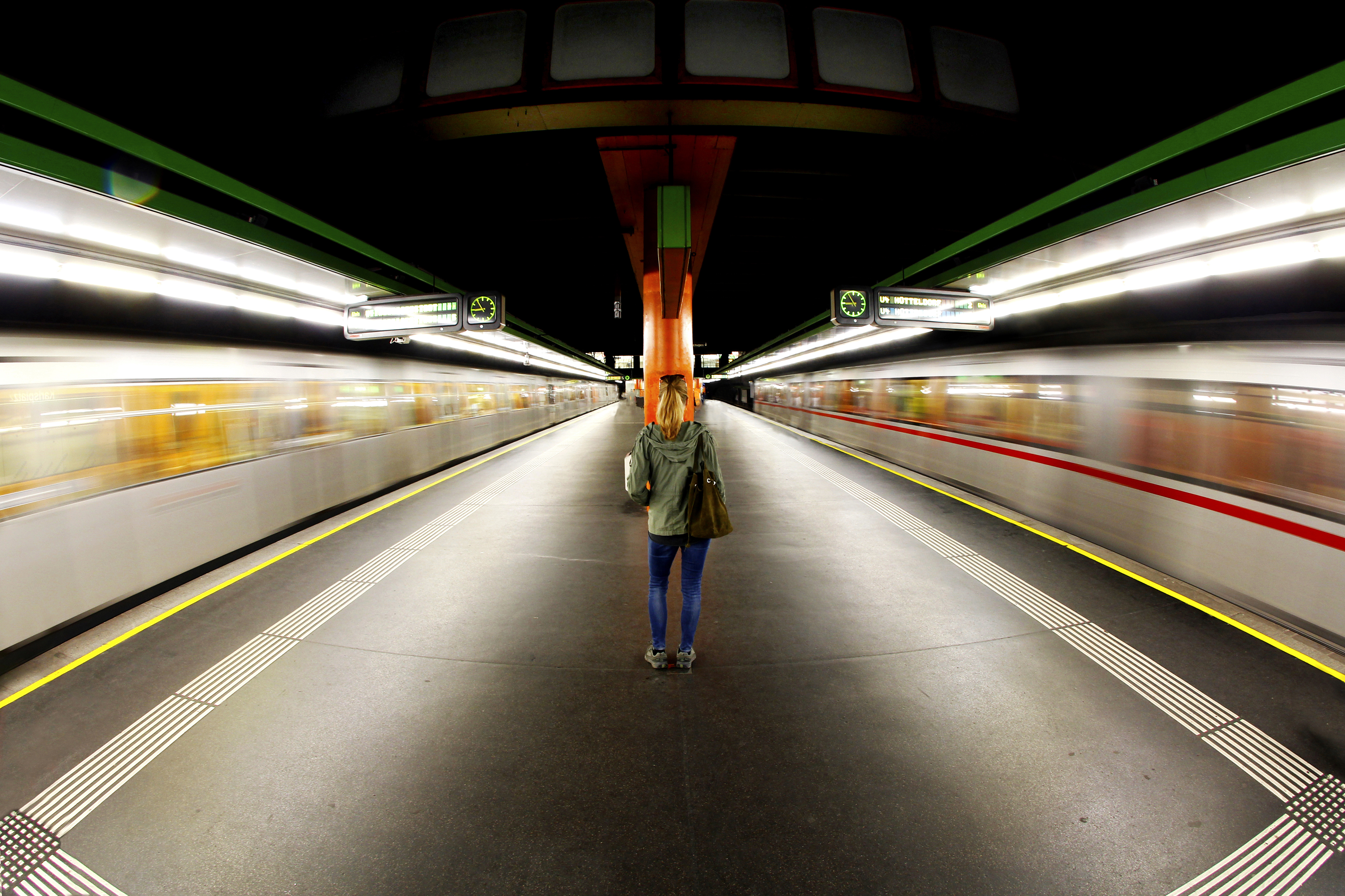 Woman standing in middle of a subway station with two driving subway trains.