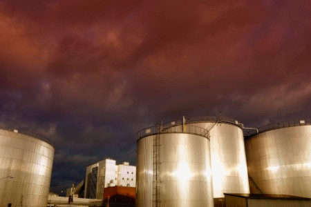 oil and gas storage tanks at a red sunset