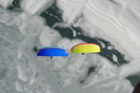 Two paragliders fly above the frozen Achensee with awesome ice-structures.