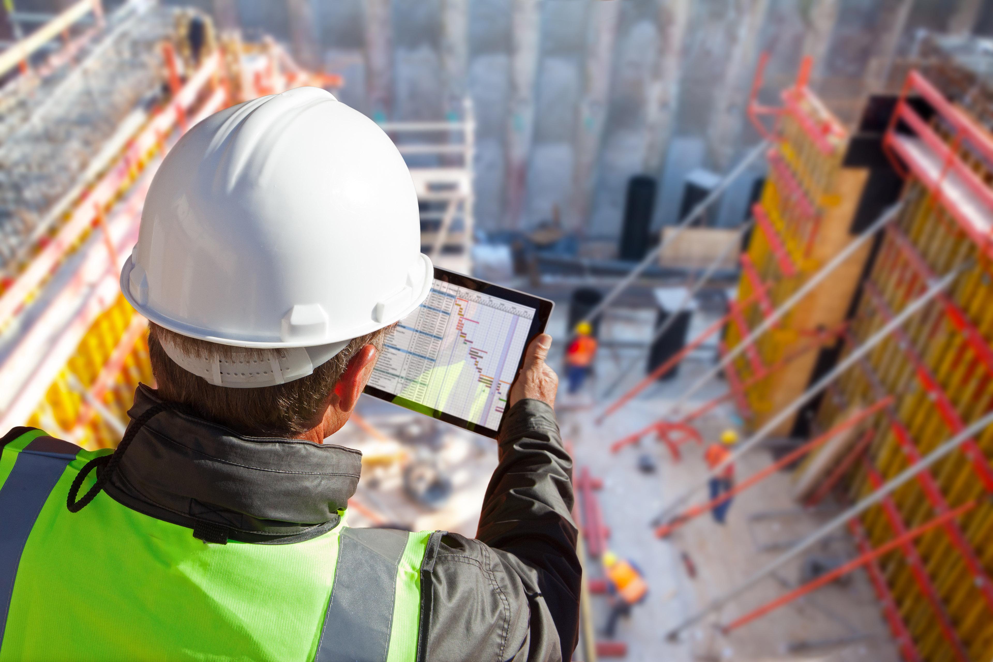 Engenheiro segurando tablet e fiscalizando obra de cima de prédio