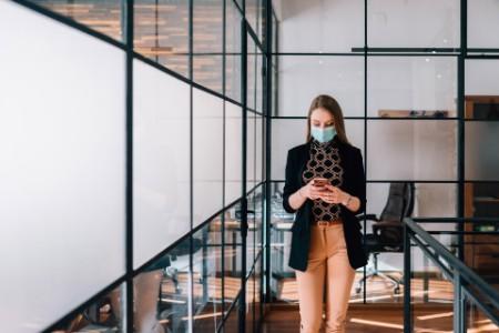 Nő maszkban áll az irodában
