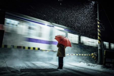 Woman in a snow storm stands at railway crossing