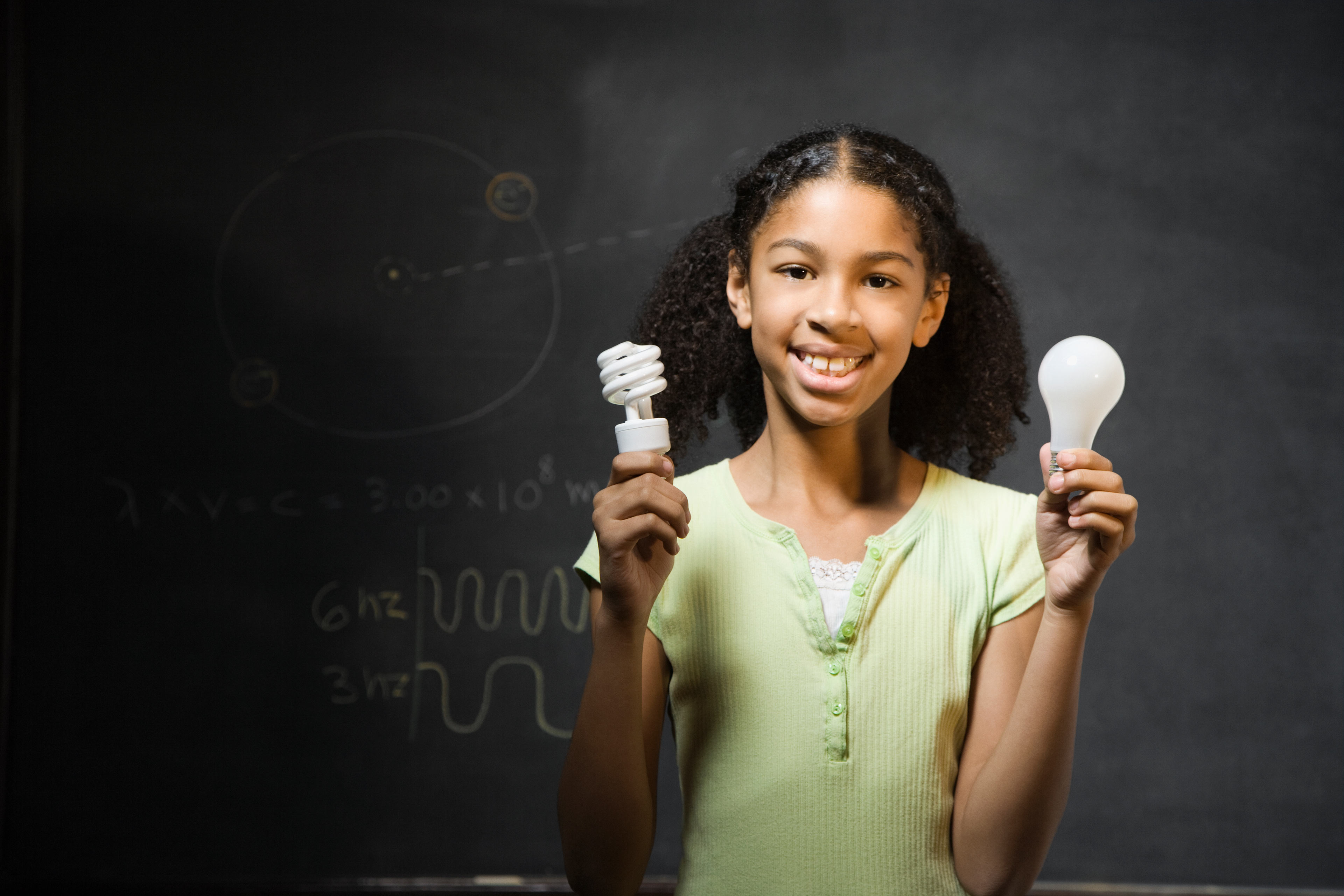 Mixed Race girl holding light bulbs