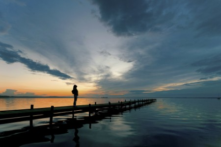 Woman on Lakeside Jetty with majestic Sunset Cloudscape