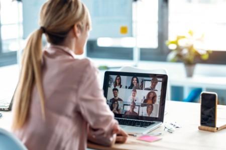 Kvinne foran PC med møte på skjerm