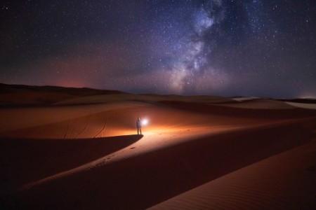 Mann i ørken titter på stjernene