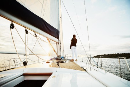 Woman stands foredeck sailboat watching sunset