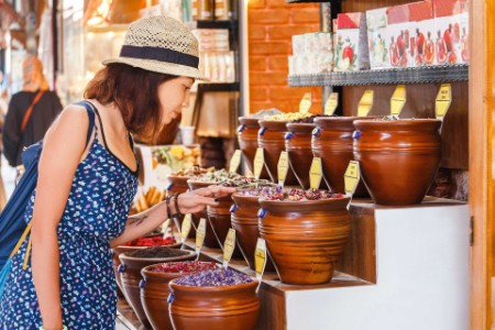 Smiling female customer choosing spices in outdoor market