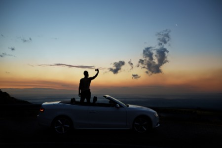 EY person taking selfie photo by standing in the car at sunset