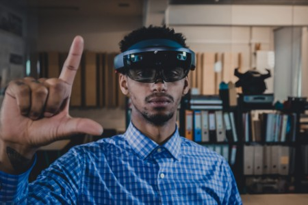 EY young man using holo glasses to experience the virtual