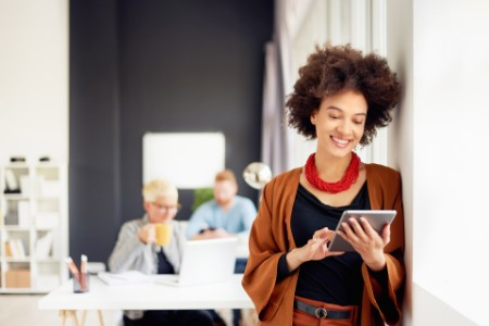 EY woman smiling while browsing in ipad