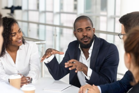 Young boss leading corporate team during briefing in boardroom