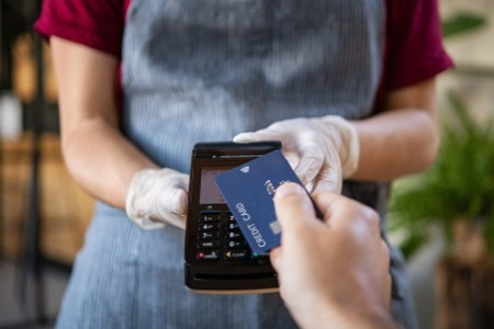 Waitress holding credit card reader machine and wearing protective disposable gloves with client hol