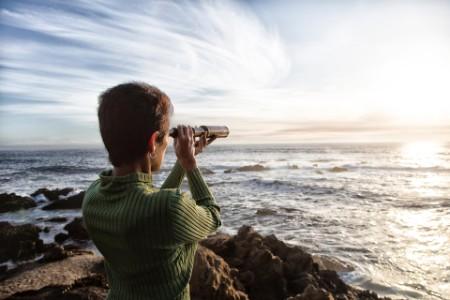 Woman looking the sea using telescope