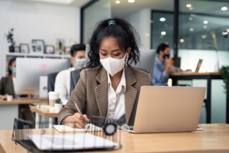 Businesswoman working wearing mask