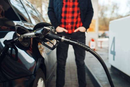 EY person filling gas at gas-station to his vehicle
