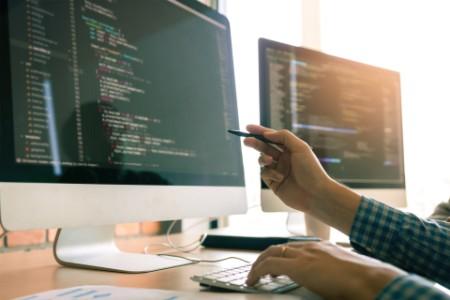 Programming code on computer desk in office room