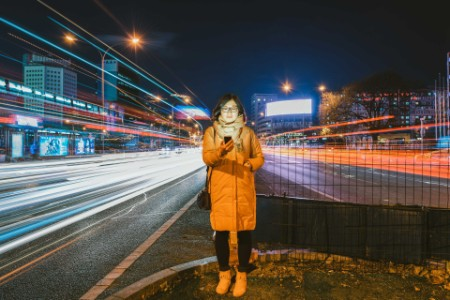 Woman holding the mobile in busy street road at night