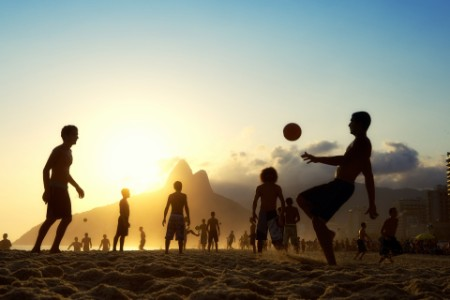 Sunset silhouettes playing Altinho Futebol beach Football