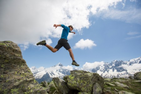 EY Athlete jumping on rocky mountains