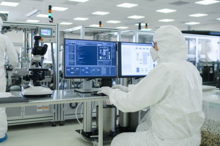 Scientists in Sterile suit analyzing data in laboratory