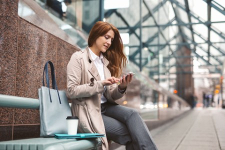EY business woman using mobile at platform