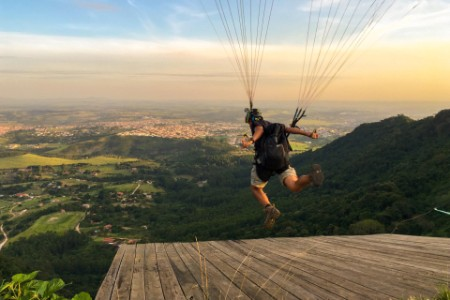 Person paragliding from top of the mountain