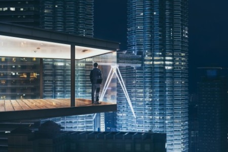EY business man standing at hotel balcony at night light