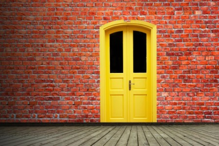 EY abstract brick wall with yellow colored door