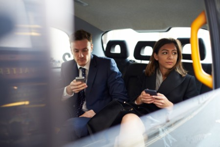 EY business people using mobile phone in the car