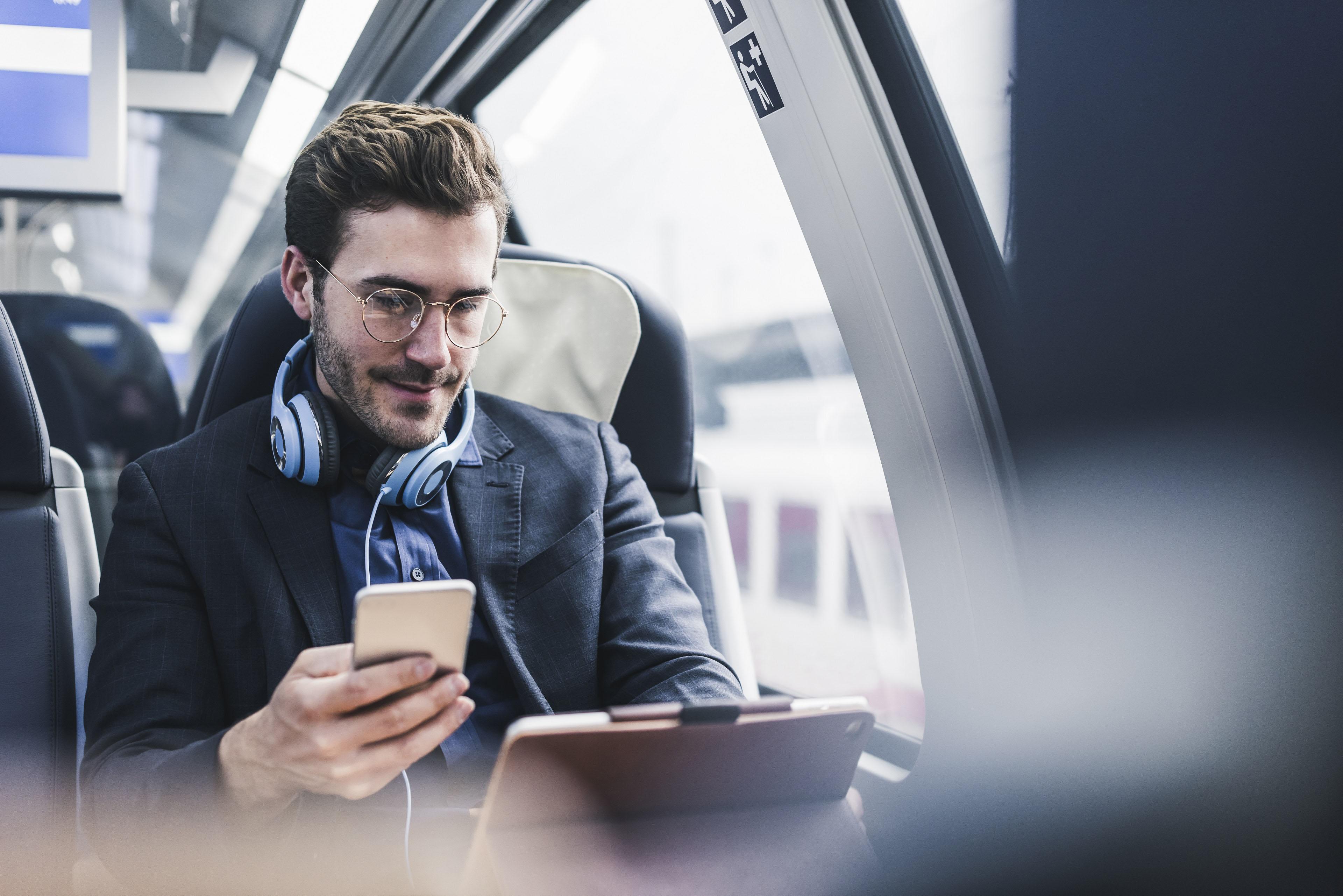 Женщина в очках проверяет свой телефон в метро