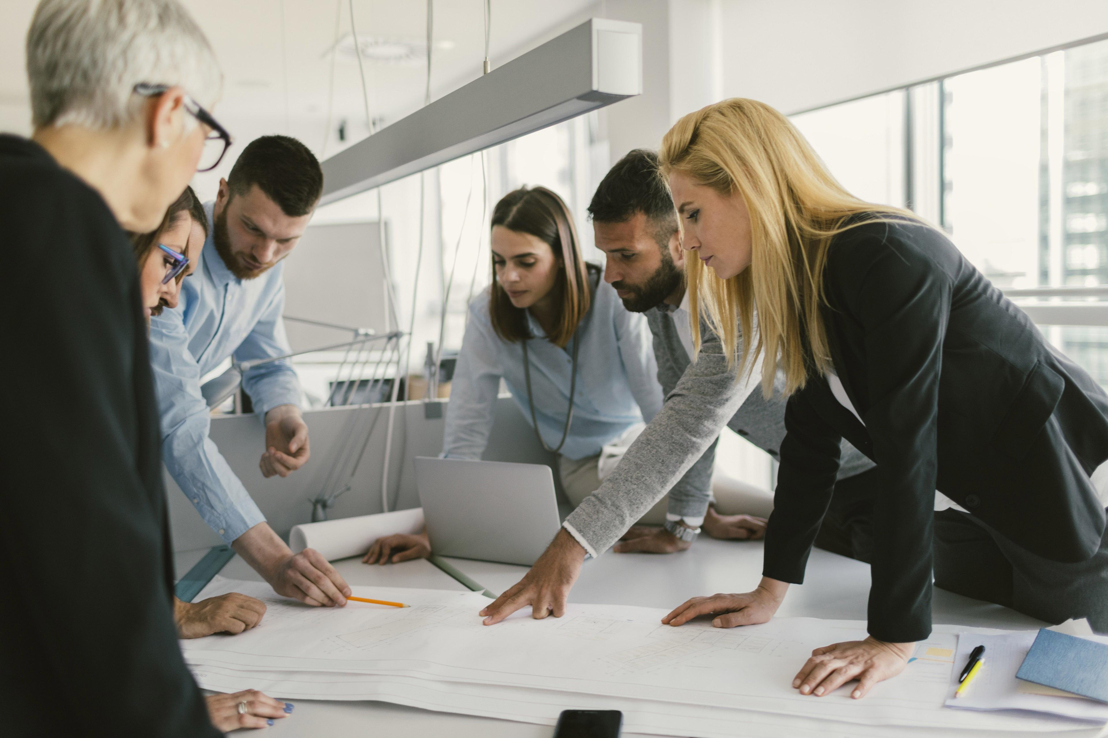 Люди с ноутбуками сидят в креслах современного офиса