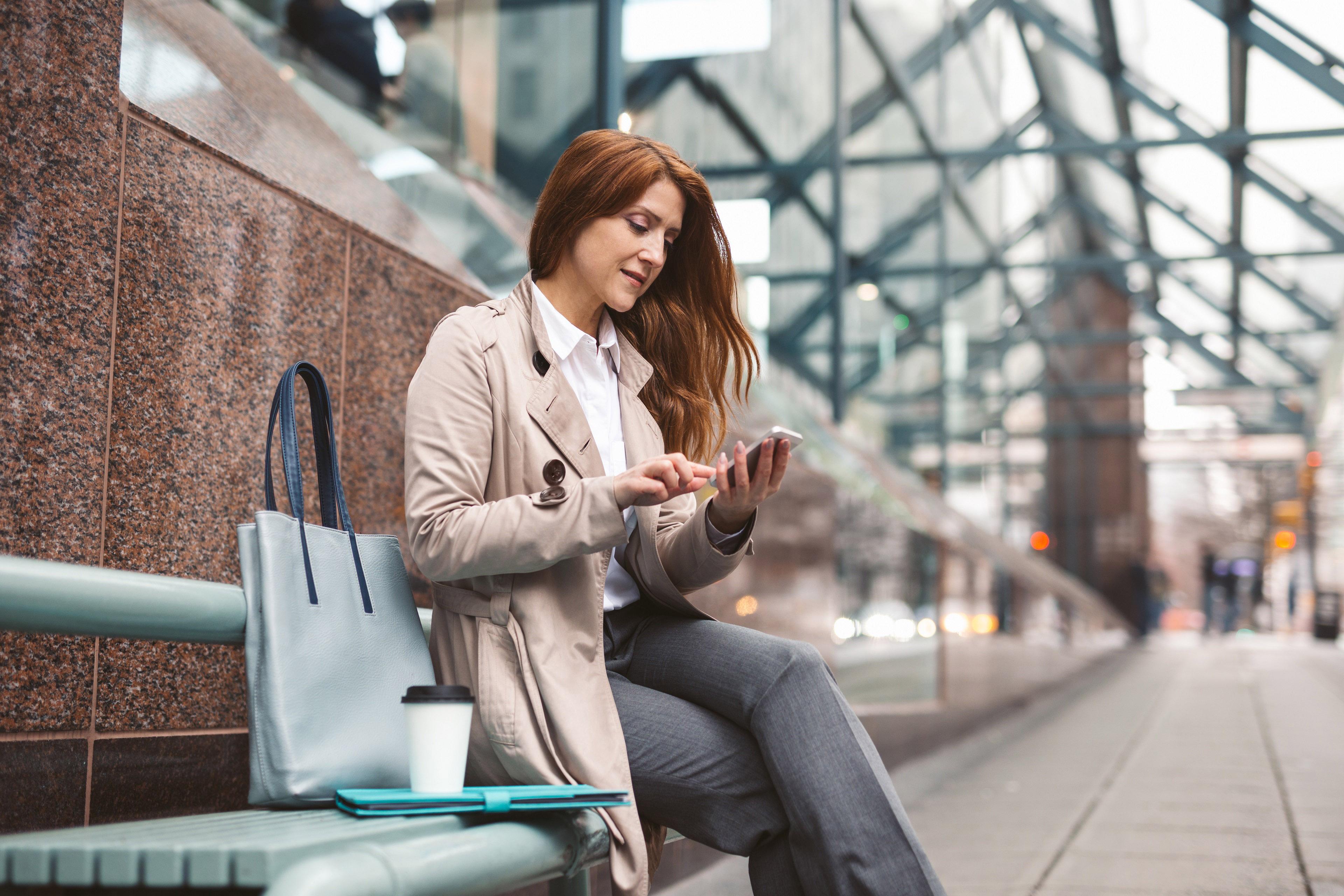 Женщина в платке смотрит в экран телефона