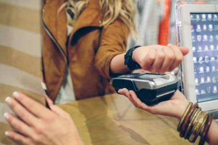 женщина оплачивает покупки с помощью смарт часов