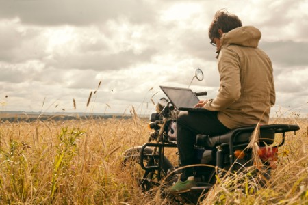 EY Mari man using laptop on motorcycle in rural field